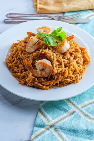 Tail-on shrimp Spanish rice with vermicelli pasta on marble kitchen table Banco de Imagens