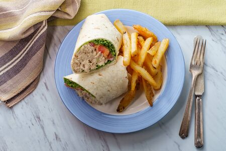 Tuna salad wrap sandwich with french fried potatoes Imagens