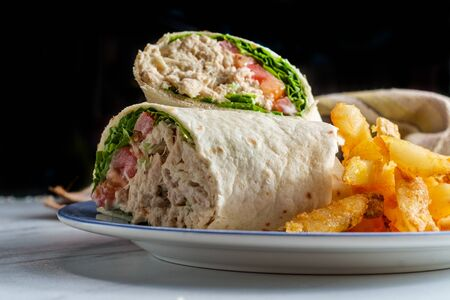 Tuna salad wrap sandwich with french fried potatoes