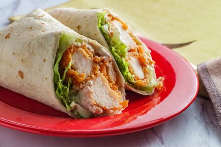 Crispy chicken Caesar salad wrap sandwich with romaine lettuce