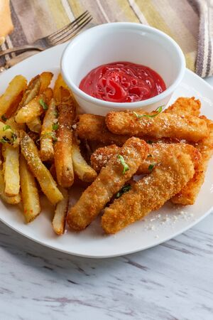 American fish sticks and french fries with ketchup on marble kitchen table