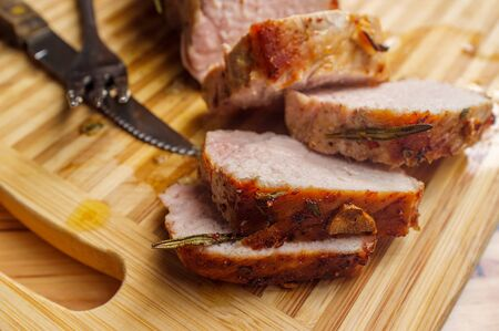 Sliced honey mustard roast pork tenderloin on wooden kitchen cutting board
