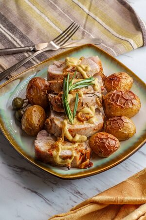 Sliced honey mustard roast pork tenderloin with baby potatoes and caperberry garnish