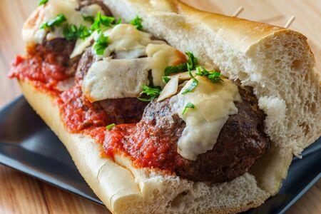 Italian meatball parmesan hero sandwich on a torpedo roll with parsley garnish