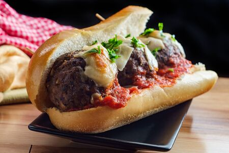 Italian meatball parmesan hero sandwich on a torpedo roll with parsley garnish