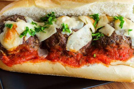 Italian meatball parmesan hero sandwich on a torpedo roll with parsley garnish Stock Photo