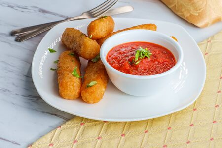 Breaded fried mozzarella cheese sticks with tomato marinara dipping sauce