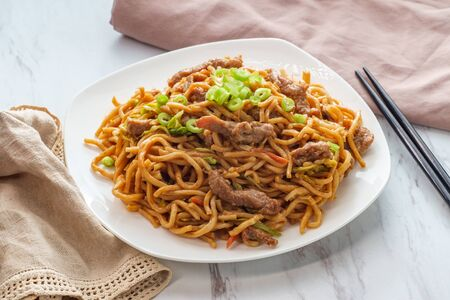 Eating Chinese beef lo mein noodles with chopsticks