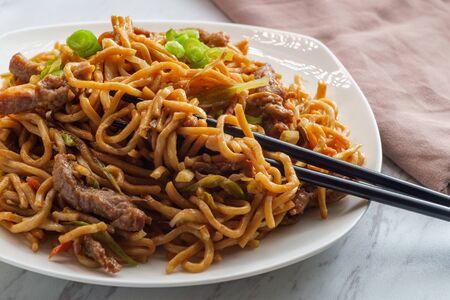 Chinesisches Rindfleisch lo mein Nudeln mit Stäbchen essen