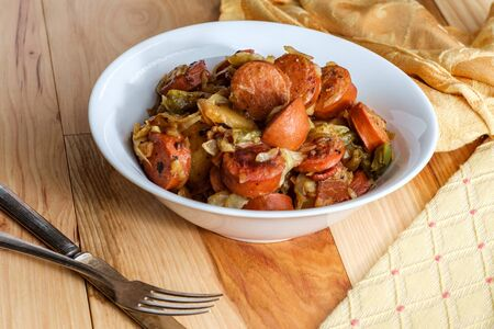 Patatas kielbasa polacas, cebollas y pimientos picadillo con ensalada de repollo