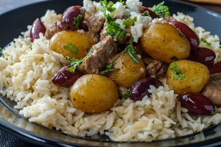 Greek lamb stew marinated in a white wine salmoriglio sauce with new potatoes kalamata olives feta cheese and mint garnish Stock Photo