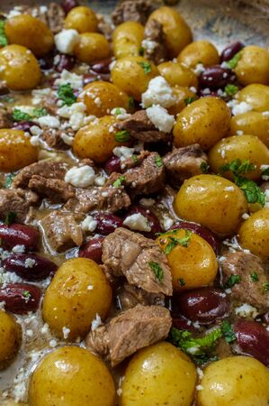 Cooking Greek lamb stew marinated in a white wine salmoriglio sauce with new potatoes kalamata olives feta cheese and mint garnish