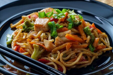 Eating Chinese chicken chow mein noodles with chopsticks