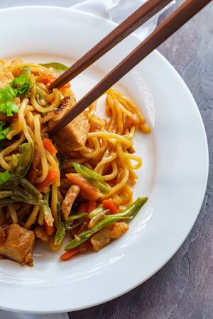 Eating Japanese chicken yakisoba noodles with chopsticks Stock Photo
