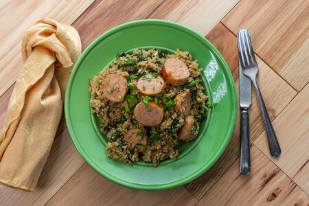 Chicken sausage with spinach and quinoa on wooden kitchen table
