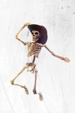 Silly dancing medical skeleton wearing cowboy hat on grunge vintage background Standard-Bild