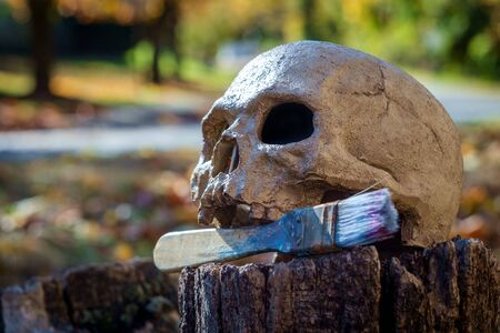 Starving artist metaphor concept human skull with used paintbrush
