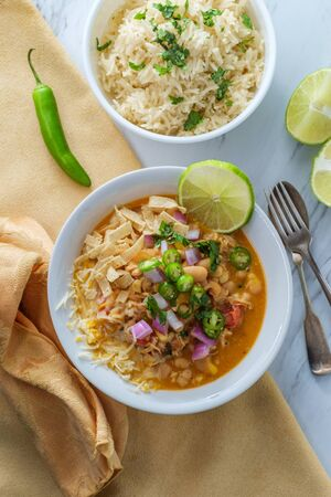 White navy bean chicken chili with tortilla strips lime cilantro and shredded cheese garnish