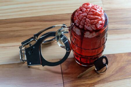 Human brain in beer mug soaking with car keys and handcuffs for alcoholism addiction concept