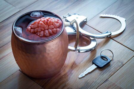 Cerveau humain dans la tasse de cocktail de mule de Moscou en cuivre imbibant de clés de voiture et de menottes pour le concept de dépendance à l'alcoolisme Banque d'images