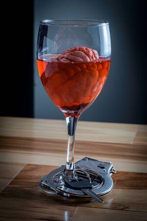 Cerveau humain dans un verre de vin rouge imbibé de clés de voiture et de menottes pour le concept de dépendance à l'alcoolisme