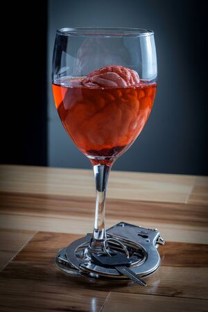 Human brain in red wine glass soaking with car keys and handcuffs for alcoholism addiction concept