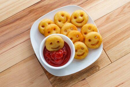 Caras sonrientes de papa frita francesa feliz con salsa de tomate