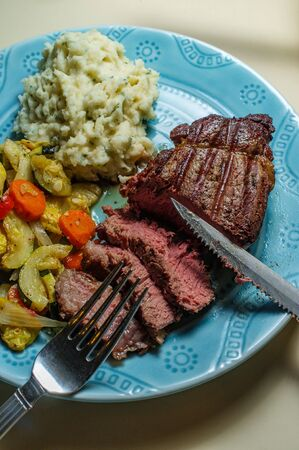 Filet mignon steak dinner with mashed potatoes and grilled vegetables