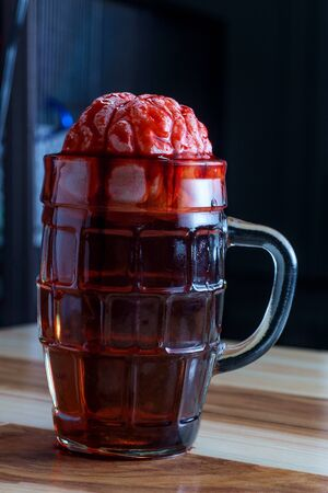 Human brain in beer mug soaking for alcoholism addiction concept