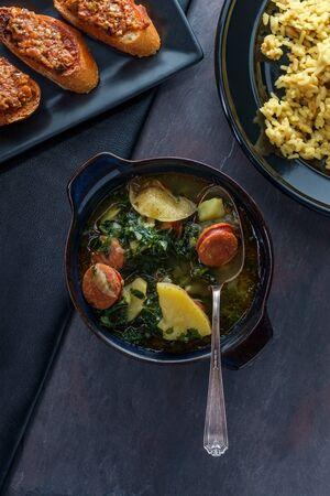 Traditional Portuguese caldo verde chourico soup with orzo rice pilaf and petiscos Imagens
