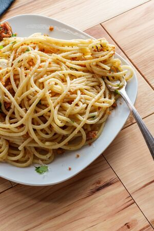 Italian spaghetti pasta mollicata with breadcrumbs parmesan cheese in an anchovy white wine sauce