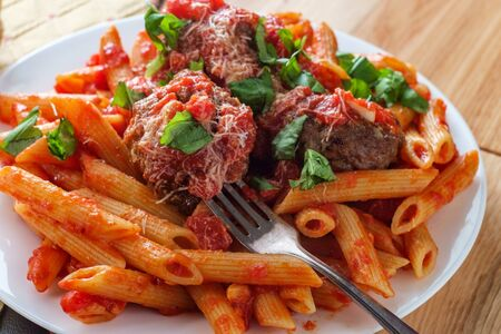 Italian penne rigate pasta with sugo all'arrabbiata sauce and meatballs garnished with chopped basil and parmesan cheese