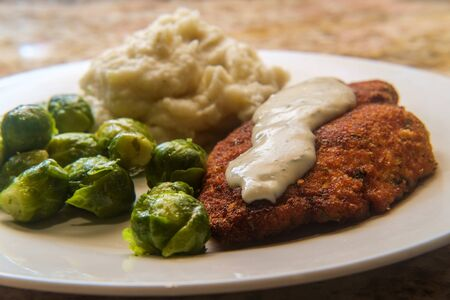 Baked breaded chicken cutlets with brussels sprouts and mashed potatoes
