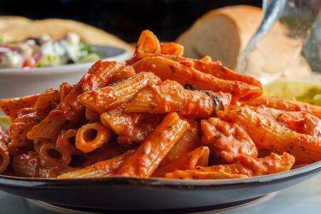 Italian penne pasta in creamy vodka tomato sauce with grilled chicken on marble kitchen table