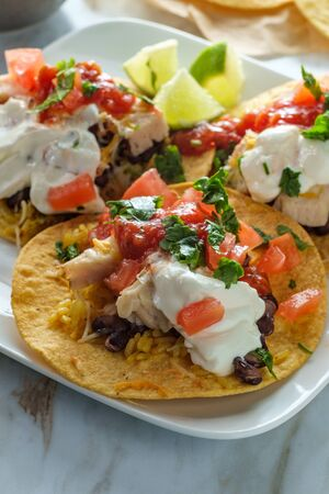 Mexican chicken tostada flat tacos with rice black beans salsa and sour cream