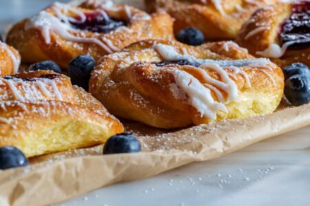Blueberry glazed danish dessert pastries with icing and powdered sugar