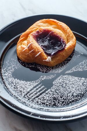 Blueberry glazed danish dessert pastry with icing and powdered sugar