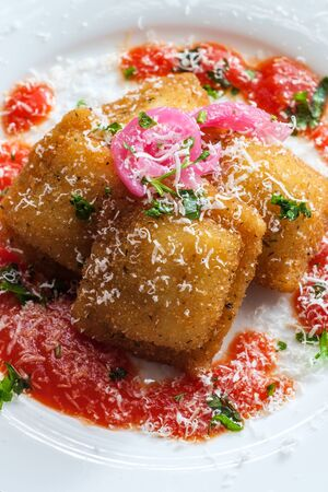 Breaded fried Italian ravioli topped with pickled red onions and grated pecorino romano cheese and hot marinara tomato sauce Stock Photo
