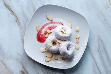 Powdered sugar cake doughnuts with holes served with raspberry jam and slivered almonds