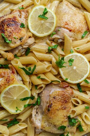 Skin-on bone-in chicken thigh piccata with penne pasta one-pot dish Banque d'images