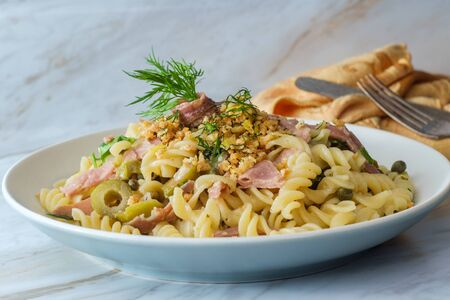 Castelvetrano olives Italian fusilli pasta mollicata with capers and prosciutto garnished with breadcrumbs in an anchovy white wine sauce