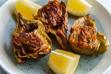 Italian fried halved artichoke with lemon wedges