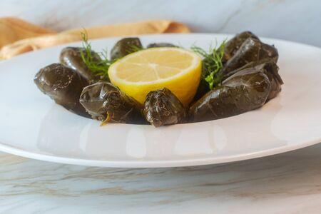 Armenian yaprak dolma, stuffed grape leaves garnished with lemon and fresh dill