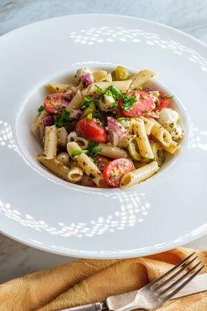 Gluten free Italian pesto pasta salad with pearl mozzarella cheese balls and halved cherry tomatoes Archivio Fotografico