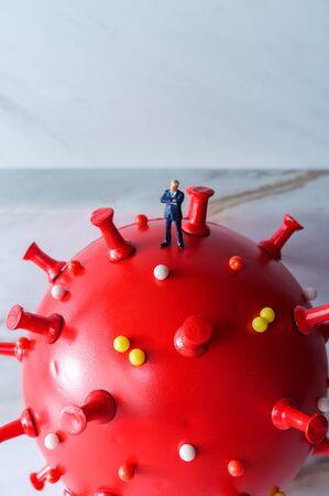 Businessman standing on top of the deadly coronavirus Foto de archivo