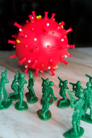 Green toy army men attack and fight off the coronavirus as metaphor for human immune system