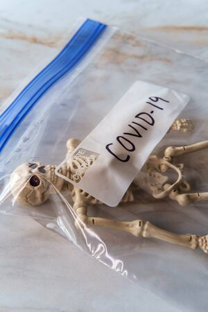 Toy skeleton in plastic bag labeled COVID-19 to symbolize the death toll from the coronavirus