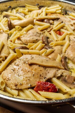 Cooking creamy Italian chicken marsala with King oyster mushrooms and sundried tomatoes served with penne rigate pasta