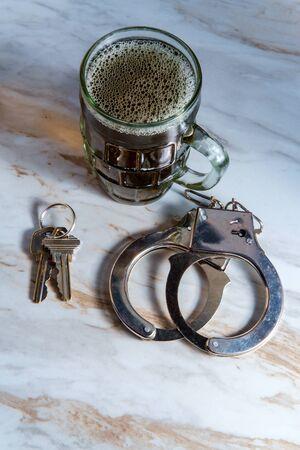 Mug of beer with handcuffs and keys symbolizing drunk driving arrest Foto de archivo