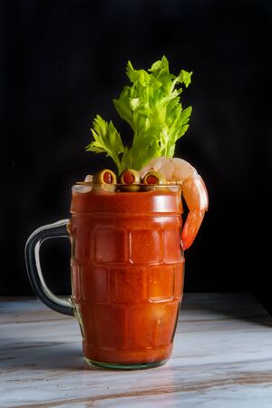 Bloody Mary vodka cocktail in a beer stein with shrimp garnish on marble kitchen table